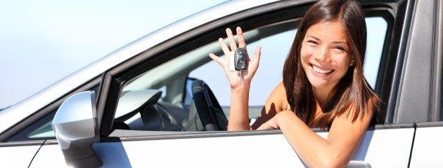 young female driving in car seat smiling and showing car keys