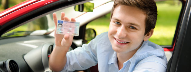 Young driver showing his new driver's license